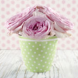 Pink flowers in a green polkadot vase Royalty Free Stock Photos