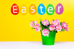 Pink flowers in green pot on table, word Easter Royalty Free Stock Image