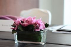 Pink flowers on a meeting room table. Pink flowers in a glass vase sit on a brown table in a business meeting Royalty Free Stock Images