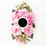 Pink flowers with mug of coffee on white background. Floral lifestyle composition. Flat lay, Top view. Pink flowers with mug of coffee on white background Royalty Free Stock Images