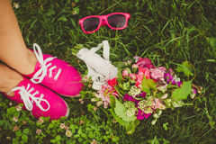 Pink flowers, pink glasses, pink shoes. Wedding bouquet with pink flowers, pink glasses, pink shoes on the green grass Royalty Free Stock Photos