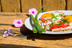 Pink flowers, a plate with eggs, green onions and tomatoes Stock Photos