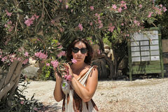Pink flowers on a tree Oleander and woman in sunglasses Royalty Free Stock Photos