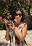 Pink flowers on a tree Oleander and woman in sunglasses Royalty Free Stock Photography
