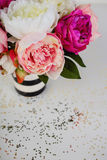 Pink Flowers in Vase. Bright Pink and white flowers in a black and white striped vase. Gold glitter sprinkled around flowers and vase Stock Images