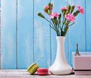 Pink flowers in the vase, macarons and souvenir Eiffel tower Royalty Free Stock Photography