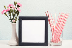 Pink flowers in a vase, paper straws and blank frame Stock Photography