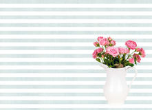 Pink flowers in white jug on watercolor blue stripes background. Royalty Free Stock Photo