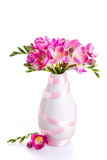 Pink flowers in a white vase decorated with ribbon Royalty Free Stock Photos