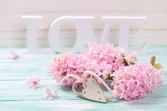Pink flowers, wooden word love and decorative heart   on turquoi. Se wooden background against white wall. Selective focus Stock Image