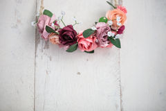 Pink flowers wraith or tiara on white wooden background. Handmade wraith or tiara made of pink and red rose flowers lying on bright white wooden background Royalty Free Stock Photography