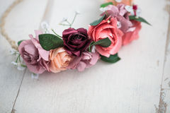 Pink flowers wraith or tiara on white wooden background. Handmade wraith or tiara made of pink and red rose flowers lying on bright white wooden background Royalty Free Stock Photo