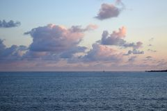 Pink fluffy clouds over the sea stock photography