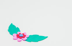 Pink foam craft flower with green leaf on white background and selective focus Royalty Free Stock Photography
