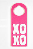 Pink Foam Door Hanger on white textured Background Royalty Free Stock Images