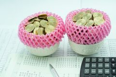 Pink foam mesh wrapped stacks gold coins in a porcelain cup. With a pen and calculator on financial documents Royalty Free Stock Image