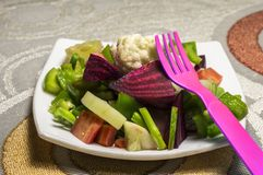 Pink fork and green salad. Green salad and a pink fork to eat it. Complete image is having salad on the table stock photo