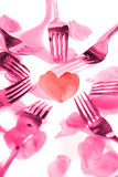 Pink forks surrounding heart shape and rose petals Royalty Free Stock Images