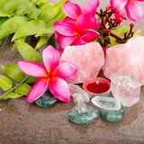 Pink Frangipani flowers and fern leaf with healing crystals Royalty Free Stock Photos