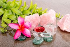 Pink Frangipani flowers and fern leaf with healing crystals. Rose quartz, clear quartz, flourite and red candle on wet brown slate background royalty free stock images