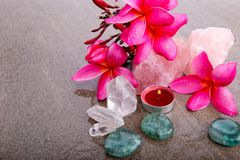 Pink Frangipani flowers with healing crystals and red candle Stock Image