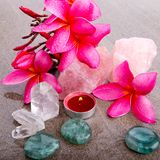 Pink Frangipani flowers with healing crystals and red candle Royalty Free Stock Image
