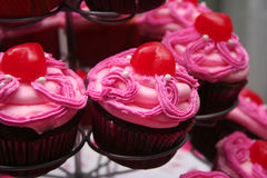 Pink Frosted Chocolate Cupcakes. Close up of Chocolate Cupcakes with Pink Frosting and Red Candy Topping Stock Photography