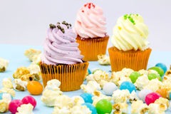 Pink frosted cupcakes on light blue background Stock Photos