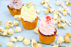 Pink frosted cupcakes on light blue background Royalty Free Stock Image