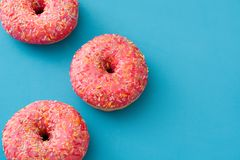 Pink frosted donut with colorful sprinkles on blue background. Top view Stock Photos