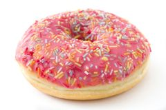 Pink frosted donut with colorful sprinkles isolated. On white background Stock Photography