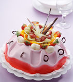 Pink fruits cake. Pink color cake with many cut fruits Stock Image