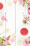 Pink fruity tea and pastel french macarons cakes on white Stock Photo