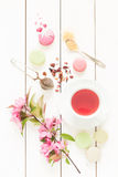 Pink fruity tea and pastel french macarons cakes on white Royalty Free Stock Photo