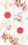 Pink fruity tea and pastel french macarons cakes on white Royalty Free Stock Images