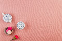 Pink french macaroons, in a bowl with fuchsia incarnation flower and chinaware teapot and bowl over a pink tablecloth background. Pink and fuchsia magenta french stock image