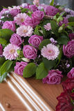 Pink Funeral flowers on a casket. Pink flower arrangement and red roses on a wooden casket royalty free stock images