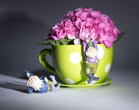 Pink Fushia Hydrangeas. In a yellow polka dot coffee mug with garden gnomes. Deep shadows created by painting with light Royalty Free Stock Photography