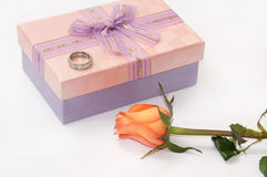 Pink gift box with bow and engagement ring and orange rose Stock Image