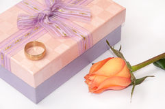 Pink gift box with bow and golden ring and orange rose Stock Photos