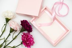 Pink gift box with carnations on white royalty free stock photo