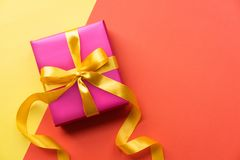 Pink gift box on color background. Yellow and orange background with present. Copy space. Pink gift box on color background. Yellow and orange background with royalty free stock photos