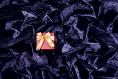 Pink gift box on a delicate blue silk surface with highlights, arranged in waves and pleats stock photo