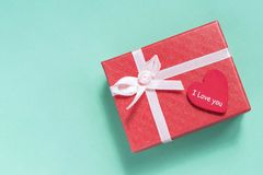 Pink gift box with heart on blue background.  royalty free stock photography