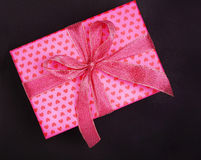 Pink gift box in heart pattern on black Stock Photography