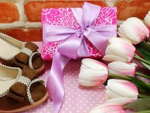 Pink gift box and ladies shoes on pink polka dot background Royalty Free Stock Photo