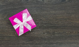 Pink gift box with light pink bow on wooden background Royalty Free Stock Images