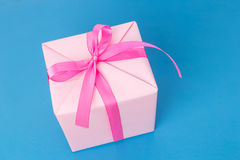 Pink gift box with ribbon on blue background. Beautiful pink gift box with ribbon on blue background Royalty Free Stock Photos
