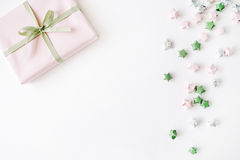 Pink gift box with ribbon and bow on white decorated with tinsel background. Flat lat, top view Royalty Free Stock Images