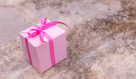 Pink gift box with ribbon. On concrete  background Royalty Free Stock Photography